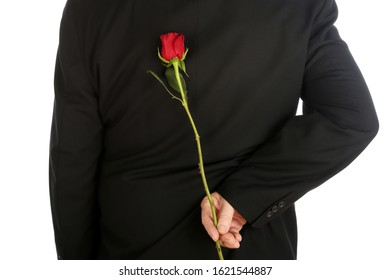 Man with a Single Red Rose. A man in a suit has a Red Long Stem Rose behind his back as a surprise gift. Isolated on white. Room for text. Clipping Path. Love and Romance. Valentines Day Gift.