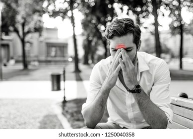 Man with sinusitis, holding his nose because of a sinus pain. Portrait of young man who is having pain in his sinus. Young man holding his head in pain. Man in shirt and tie grimacing in pain