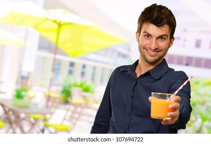 Man Sipping Juice Through Straw, Outdoor
