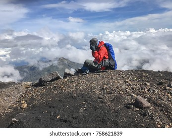 Man sit above the skyline in top of mountain