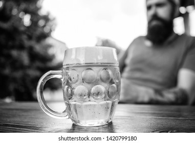 Man sit cafe terrace enjoying beer defocused. Alcohol and bar concept. Creative young brewer. Craft beer is young, urban and fashionable. Distinct beer culture. Mug cold fresh beer on table close up.