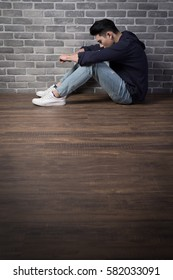 man sit and feel depressed with brick wall ,asian