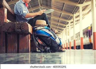 A man sit with map. travel bag at the train station.