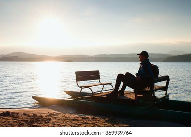 Man sit on abandoned old rusty pedal boat stuck on sand of beach. Wavy water level, island on horizon. Autumn weather at coastline