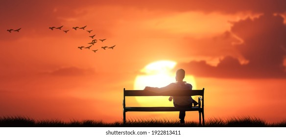 man sit on a bench on a relax in nature sunset.