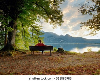 Man sit on wooden bench at mountain lake. Bank under beeches tree, mountains at horizon and in water mirror. Vintage toned photo.
