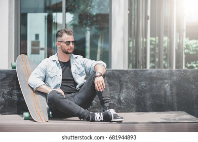 Man sit with skateboard in urban landscape