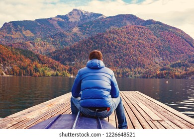 Man is siting back on the pier and watches over the lake and the mountains.