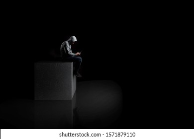 A man sits alone with a smartphone on a concrete cube in the dark