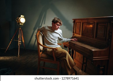 A man sits in a chair in front of the piano and a spotlight
