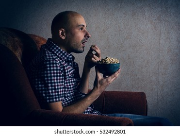 man sits in a chair and watching TV at night at home