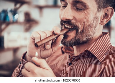 Man sits with a cigar in his mouth and lights it. Stylish man after a new haircut sits in a barbershop and smokes.