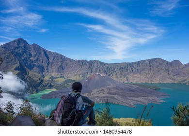 A man sits down and relax enjoying a beautiful of a Danau Segara Anak turquoise volcanic lake at Rinjani Mountain range in Indonesia.