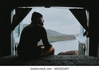 A man sits and enjoys a view from his camper van in Iceland.