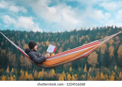 A man sits in a hammock and reads a book in a picturesque place. Mug in his right hand