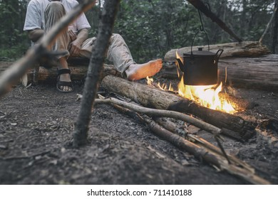 Man sits and heats his feet near the camp fire, over which the kettle hangs
