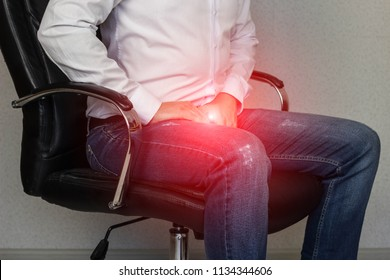 A man sits in an office chair and holds on to the groin, crotch, prostatitis
