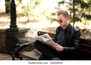 A man sits on a bench in the park and reading a newspaper. He has a serious look, leather jacket, plaid shirt.