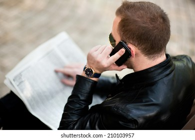 A man sits on a bench in the park and calling by phone. He has a serious look, leather jacket, plaid shirt.