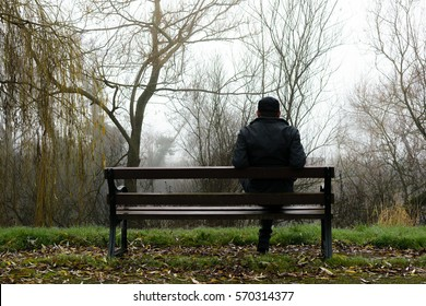 Man sits on a bench in the park on a foggy day