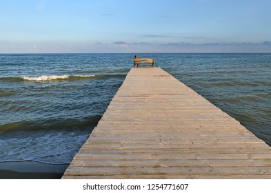 The man sits on the bridge and looks into the sea. A long wooden bridge stretches into the sea