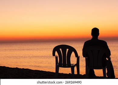 Man sits on chair alone in sunset