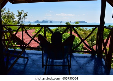 man sits on chair and see the view at the islands from his resort