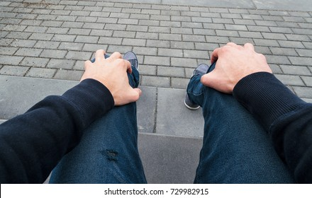 man sits on a curbstone and waits nervous for somebody, Point of view shot