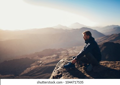 Man sits on edge of cliff on Mount Sinai and looks at sunrise in Egypt.