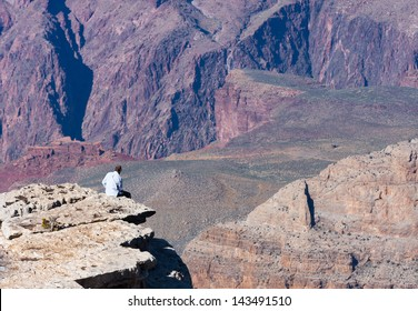 Man sits on the edge of the Grand Canyon