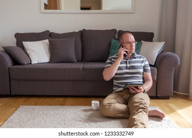 man sits on the floor near the sofa and talking on mobile phone