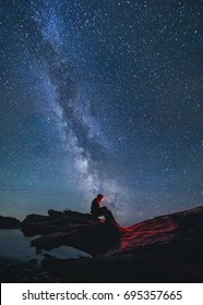 Man sits on a log underneath the stars of the Milky Way