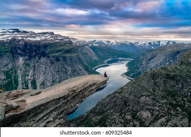 A man sits on the mountain's cliff edge of Trolltunga throning over Ringedalsvatnet watching the sunset in the snowy Norwegian mountains near Odda, Rogaland, Norway.