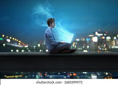Hombre se sienta en un cuaderno frente a la ciudad nocturna