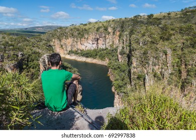 Man sits on a rock overlooking a canyon with a river on the bottom and rocky walls covered by green trees. Furnas Canyon is a common tourist destination in Brazil