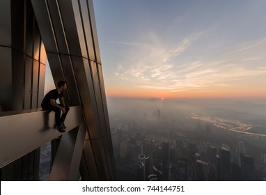 Man sits on rooftop and looks at morning cityscape, Shenzhen, China