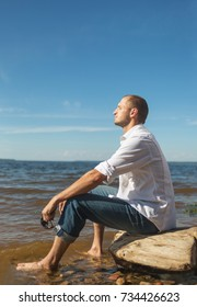 A man sits on the stone on the waterfront
