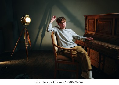A man sits on a wooden chair indoors near the piano and a spotlight in the background