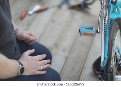 A man sits on a wooden floor and repairs a bicycle.