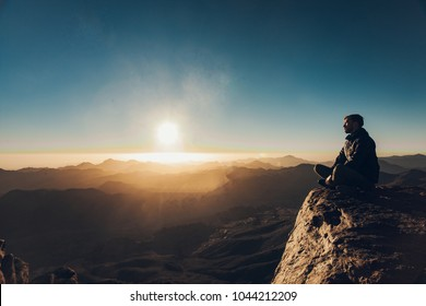 Man sits in a pose of yoga on edge of cliff on Mount Sinai and meditates against background of beautiful sunrise in Egypt.