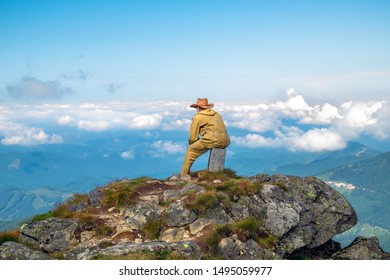 A man sits sitting on an old border post top of a mountain in a cowboy hat and looks into the distance to where he has to go. Man in mountain suit. Male on top of the mountain.