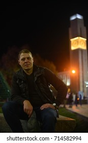 Man sits smiling against the background of the evening cityscape