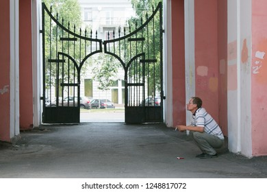 A man sits and smokes in the arch between the houses. The offender is waiting for the victim smokes in the aisle between the buildings.