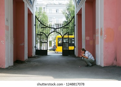 A man sits and smokes in the arch between the houses. The offender is waiting for the victim smokes in the aisle between the buildings