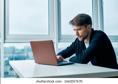 A man sits at a table in front of open laptop near the window
