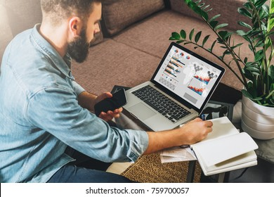 Man sits at table,working,holds smartphone,uses laptop with graphs, charts, diagrams on screen and makes notes in his notebook.Online marketing, education, e-learning, e-commerce. Startup, planning.