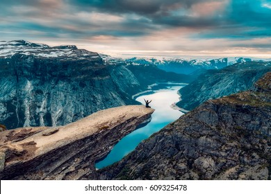 A man sits while throwing his arms in the air on the mountain's cliff edge of Trolltunga throning over Ringedalsvatnet watching the sunset in the snowy Norwegian mountains near Odda, Rogaland, Norway.