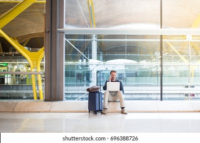 man sitting at the airport using laptop and mobile phone next to the window.