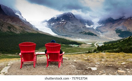 Man sitting allone on a red chair in the canadian rocky mountains
