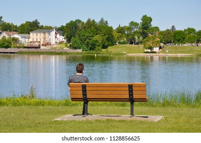 Man sitting alone in the bench facing the lake